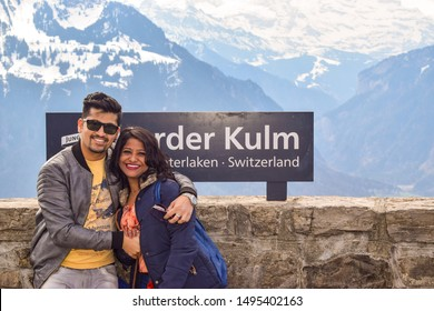 Interlaken, Switzerland, 2019 : Indian Couple in woolen wear Posing in front of Harder Kulm Sign Board in different poses. The said location is a famous tourist destination in Switzerland