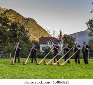 Interlaken, Switzerland - August 23, 2016: Players of traditional alphorn in a public park. In the background, the Jungfrau (4,158 m - 13,642 ft).