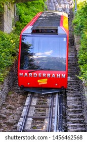 Interlaken, Switzerland - July 16 2019: Red cable car driving downhill from Harder Kulm, Top of Interlaken. Funicular drives tourists up and down from popular view point. Transportation, tourism.