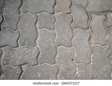 Interlocking paving with gray and white concrete blocks. Stones of the pavement of an urban street
