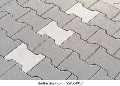Interlocking paving with gray and white concrete blocks; Concrete products; Construction industry; Paved ground