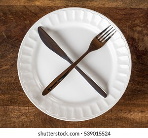 Intermittent fasting concept with knife and fork showing cross symbol on white plate against wooden table, top view