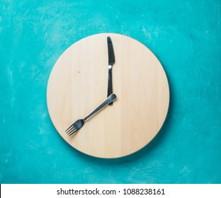 Intermittent fasting and skip breakfast concept - empty wooden round tray or trencher with cutlery as clock hands on blue background. Eight hour feeding window concept or breakfast time concept