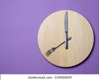 Intermittent fasting and skip breakfast concept - wooden round tray or trencher with cutlery as clock hands on lilac background. Eight hour feeding window concept or breakfast time concept. Copy space