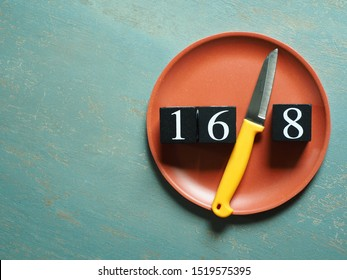 Intermittent Fasting theme represented by yellow knife between black painted wooden dice with white number 16 and 8 on red plate over vintage green background. Popular health and fitness trend.