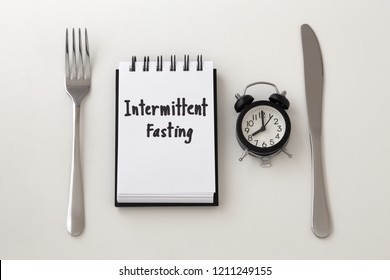 Intermittent fasting word on notepad with clock, fork and knife, weight loss plan