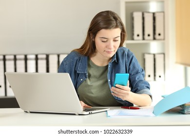 Intern checking phone message sitting in a desktop at office
