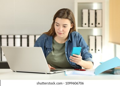 Intern working with a smart phone and a laptop on a desktop at office