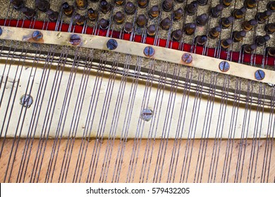 The internal components of an old piano with drops of water on the surface