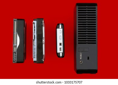 Internal hard drives and external hdd on a red background. Storage technology. Computer concept