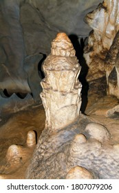 Internal images of caves, with geological formations of water dripping from the ceiling, forming stalactites and stalagmites formed on the floor. Geometric shapes and designs on the rock.