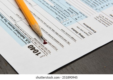 Internal Revenue Service form 1040 with sharpened pencil & drop of blood laid atop left-hand corner