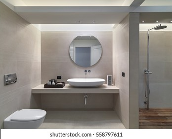 internal shots of a modern bathroom in foreground the counter top washbasin whose walls are coated of pink marble