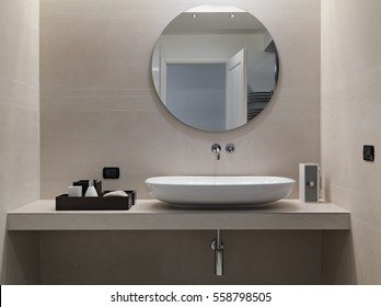internal shots of a modern bathroom in foreground of counter top washbasin whose walls are coated of pink marble