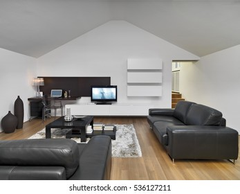 internal shots of a modern living room in the mansard in foreground the leather sofa and wooden floor