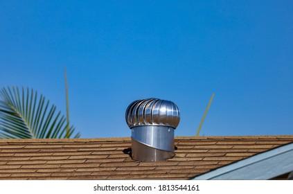 An internally braced aluminum wind turbine on top of a house's shingle roof.