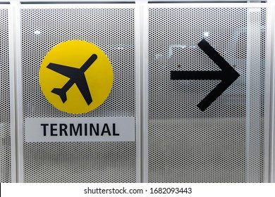 At an international airport, a temporary metal wall has been erected, and on the wall in a sign indicating which way to go for the terminal.