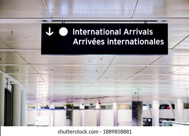 International arrivals sign board in english and french at airport terminal hall. Canada government open border for international travellers visitors to be fully vaccinated with vaccine passport.
