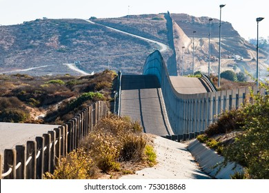 The international border wall between San Diego, California and Tijuana, Mexico, as it begins its journey from the Pacific coast over rolling hills.
