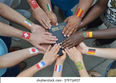 International brothers and sisters in Christ with different flags painted on their arms holding a bible together.