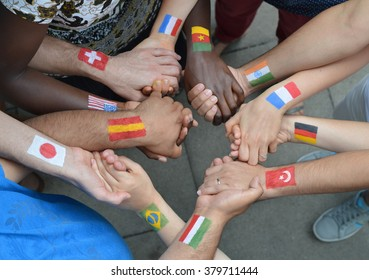 International brothers and sisters with different flags painted on their arms standing in a circle together and holding hands.