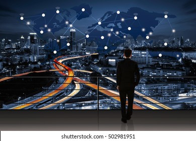 International business concept with businessman standing on a roof and looking at city background with network on map
