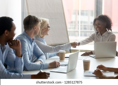 International company members starting negotiations with handshake, mixed race boss greeting or congratulating mature businesswoman client shaking hands express regard and thanks for the cooperation