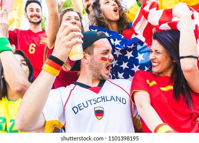 International couple celebrating together at stadium during a match. Multi ethnic group of people, fans and friends, enjoying football competition. Achievement and success concepts