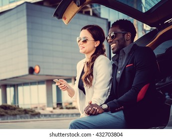 International couple with smartphone near car in downtown.