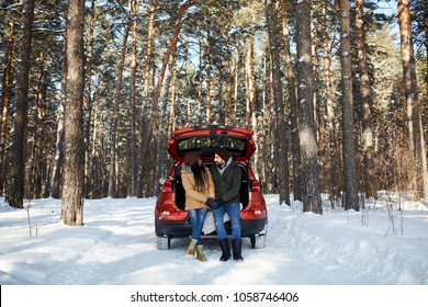 International couple in the winter forest. African-American and white man sitting in the car and having fun