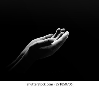 International day for the eradication of poverty concept: Black and white poverty hands opening with palms up on dark room background