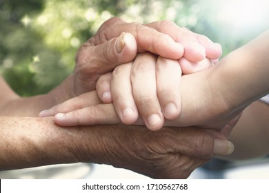 International Day of Families concept: carer hand holding elder hand in hospice care