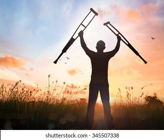 International Day of Persons with Disabilities (IDPD) concept: Silhouette a disabled man standing up and raising his crutches at meadow autumn sunset background
