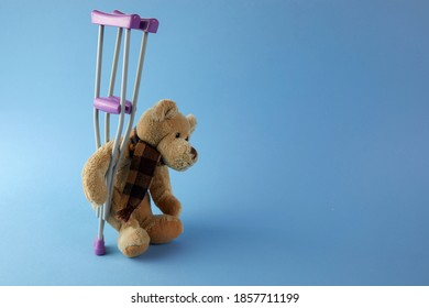 International day of persons with disabilities. Teddy bear with crutches on blue background.