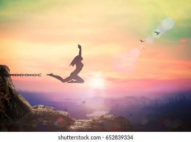 International day for the remembrance of the slave trade and its abolition concept: Silhouette of victorious woman jumping and broken chains with her hands raised at mountain autumn sunset background