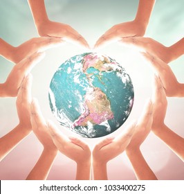 International day for tolerance concept: Heart shape of hands holding earth globe over blurred nature background. Elements of this image furnished by NASA