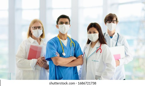 Photo of International doctor team. Hospital medical staff. Mixed race Asian and Caucasian doctor and nurse meeting. Clinic personnel wearing face mask and stethoscope. Coronavirus outbreak.