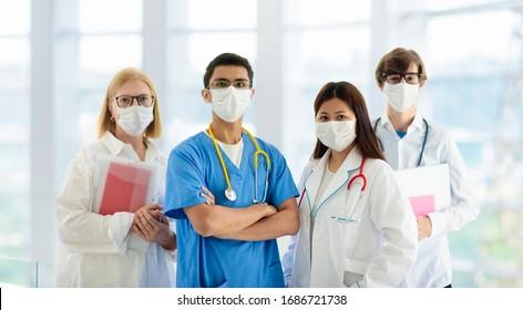 Internationales Arztteam. Krankenhausmedizinisches Personal. gemischte ethnische Zugehörigkeit Asiatische und kaukasische Ärzte und Krankenschwester treffen. Klinisches Personal mit Gesichtsmaske und Stethoskop. Ausbruch von Coronavirus.