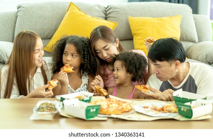 international family of happy man ,woman and children. They are having party at home, eating pizza and having fun. leisure, food and drinks, people and holidays concept. Ethnic diversity,Host family