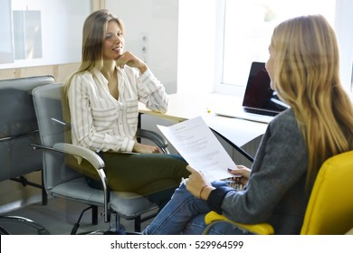 International female student discussing with her teacher strategy of coursework about marketing, making report in modern university coworking space with laptop computers and free internet access