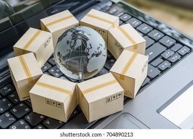 International freight or shipping service for online shopping or ecommerce concept : Paper boxes or carton put in circle around a clear crystal globe with world map on a computer notebook keyboard.