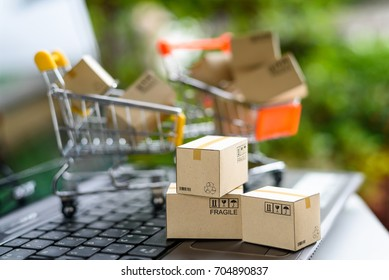 International freight or shipping service for online shopping or ecommerce concept : Paper boxes or cartons in a shopping cart on a computer notebook keyboard. Customer always buy things via internet.