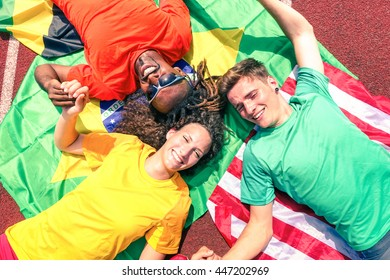International friends of sport fans circle looking up at  sky - Cheerful multiracial athletes lying on national flags after competition at stadium athletic track -  Multinational friendship concept