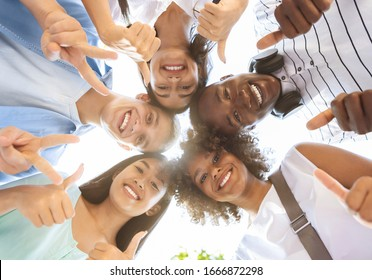 International Friendship. Group Of Joyful Multicultural Teenagers Standing In Circle, Showing Funny Gestures, Posing At Camera Outdoors, Low Angle