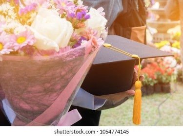 International graduate study concept : Graduation black cap on students woman hands with flowers on graduation day in university. Education certificate of Abroad program to success