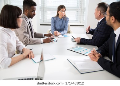 International group of business people working and communicating sitting near office desk together.