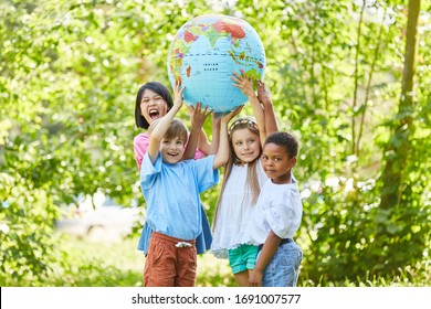 International group of children holds together a globe in nature