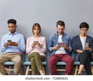 International group of four young people have internet addiction, sit in queue, use all modern techlogies and free internet conncetion for entertaining and not feel bored as wait for long time