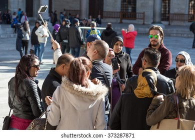 International Group of People Men and Women from different Countries visiting historical Attraction excited and taking self Portrait Photos with Mobile Phone. Istanbul, Turkey, November 18th, 2015