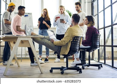 International group of professional marketing experts planning working process and developing advertising campaign while using modern technology and internet connection in loft interior office